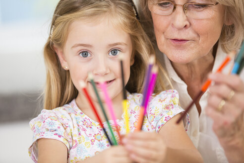 Senior woman and granddaughter showing coloured pencils - WESTF019156