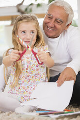 Senior man and granddaughter tinkering at home - WESTF019150