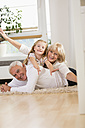 Family portrait of senior couple and granddaughter lying on the floor at home - WESTF019144