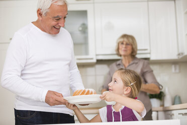 Senior couple with granddaughter in kitchen - WESTF019138