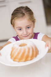 Portrait of smiling little girl taking plate with ring cake - WESTF019132