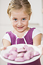 Portrait of smiling little girl offering pink cookies - WESTF019129