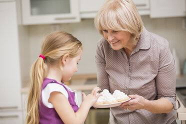 Portrait of senior woman and granddaughter with dish of waffles - WESTF019123
