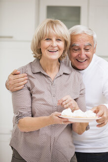 Portrait of senior couple with dish of waffles - WESTF019120
