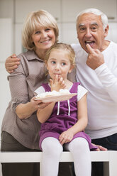 Portrait of senior couple with granddaughter in kitchen - WESTF019110