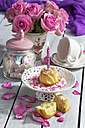 Muffin with lighted birthday candle, glass of marshmallows, cup and pink roses on table - CSF021063