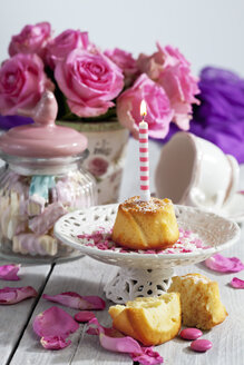 Muffin with lighted birthday candle, glass of marshmallows, cup and pink roses on table - CSF021066