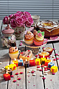 Muffins, birthday cake, cup cakes, roses, lighted birthday candles and baking decor on table - CSF021088