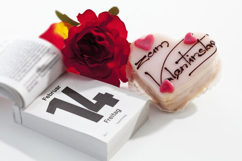 Red rose, petit four and tear-off calendar showing date of Valentine's day on white ground - CSF021095