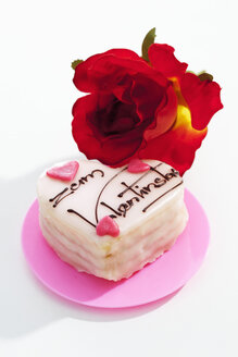 Red rose and petit four on white ground - CSF021079