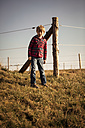 Boy standing on a meadow in front of fence - SARF000420
