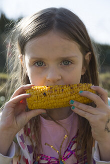 Portrait of little girl eating grilled corn cob - SARF000424