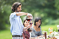 Man pouring red wine on a garden party - ABF000544