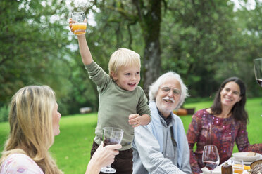 Boy holding glass on a garden party - ABF000555
