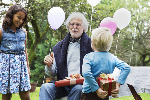Grandfather receiving gifts on birthday party in garden - ABF000564