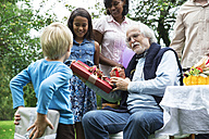 Grandfather receiving gifts on birthday party in garden - ABF000565