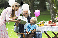 Grandfather receiving gifts on birthday party in garden - ABF000566