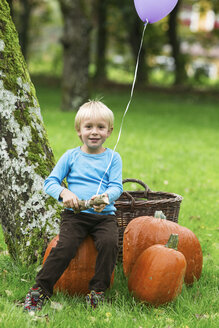 Boy with balloon and pumpkins in garden - ABF000567