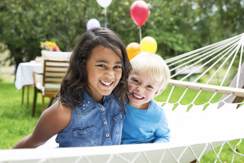 Smiling boy and girl in hammock - ABF000574