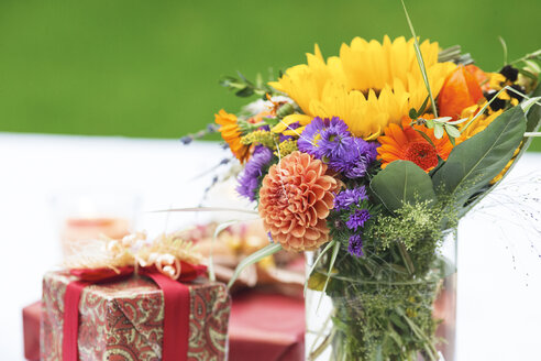 Bunch of flowers and gift on outdoor table - ABF000519
