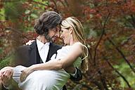 Groom carrying bride in garden - ABF000528