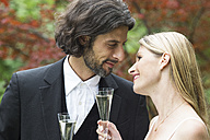 Happy bride and groom with champagne glasses in garden - ABF000530