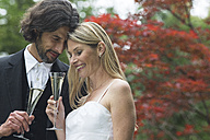 Happy bride and groom with champagne glasses in garden - ABF000532