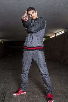Germany, portrait of young break dancer in underpass making gun sign - STS000375