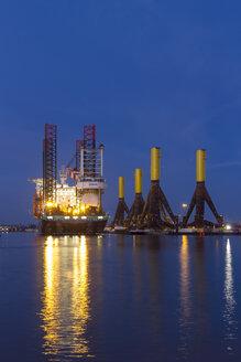 Germany, Bremerhaven, wind turbine installation vessel, tripods, blue hour - SJ000102