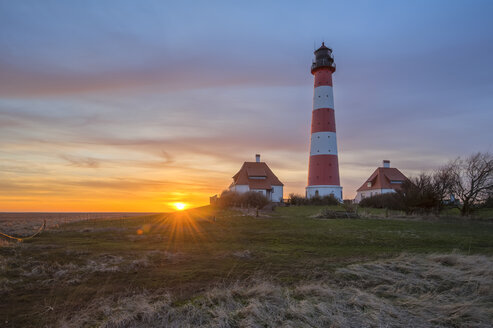Germany, Schleswig-Holstein, North Sea Coast, View of Westerheversand Lighthouse at sunset - RJF000058