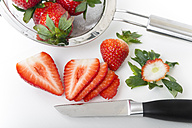Slices of strawberries, kitchen knife and strainer on white ground - CSTF000200