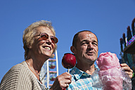 Man and woman on fair enjoying candied apple and cotton candy - GWF002696