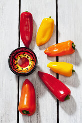Sweet bell peppers and a painted bowl on grey wooden table - CSF021119