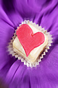 Petit four decorated with heart of marzipan on purple cloth - CSF021144