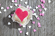 Petit four decorated with heart of marzipan on grey wood - CSF021128