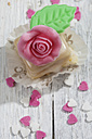 Petit four decorated with rose of marzipan on grey wood - CSF021155