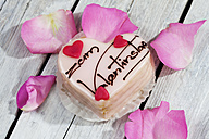 Petit four with rose petals on grey wood - CSF021148