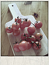 Vine tomatoes on a wooden board, studio - MYF000273