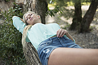 Young woman lying on tree trunk having a rest - LFOF000150