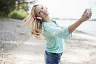 Young woman with headphones dancing on the beach - LFOF000157