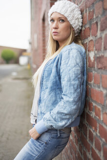 Fashionable young woman leaning at brick wall - LFOF000168