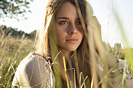 Portrait of daydreaming female teenager sitting on a meadow - LFOF000179