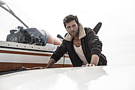 Portrait of man with leather jacket standing in front of propeller plane - MUMF000019
