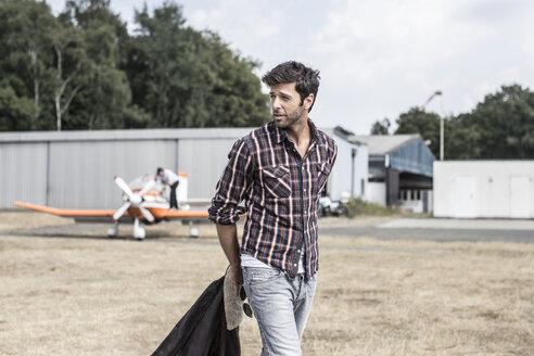Man walking in front of propeller plane - MUMF000047
