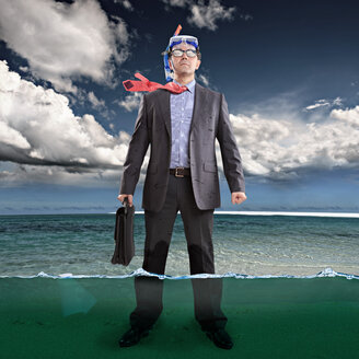 Businessman standing ankle-deep in water, wearing snorkel - VTF000189