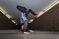 Young breakdancer performing a handstand in underpass - STSF000390