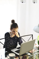 Young woman working with laptop at home - EBSF000150