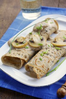 Close up of crepes filled with creamy mushroom with a glass of white wine - HAWF000024