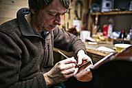 Violin maker repairing crack in cello - DIKF000088