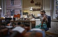 Violin maker in his workshop varnishing repaired violin - DIKF000091